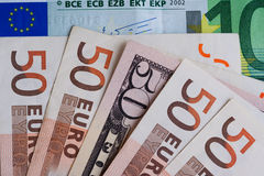 Billet de banque de 50 dollars parmi des billets de banque 50 euro Image libre de droits