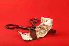 Billet de banque de coupe de ciseaux euro au-dessus de fond rouge Photos stock