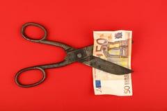 Billet de banque de coupe de ciseaux euro au-dessus de fond rouge Photographie stock
