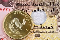 Billet de banque de dirham des cinq EAU avec une pièce de monnaie d'or de Krugerrand photographie stock