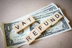 Billet de banque en bois de REMBOURSEMENT et de dollar du mot TVA de bloc Photographie stock libre de droits