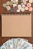 Billet de banque et pièces de monnaie avec le carnet Photo stock