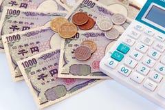 Billet de banque japonais de Yens de devise avec la pièce de monnaie et calculatrice sur le petit morceau Photos stock