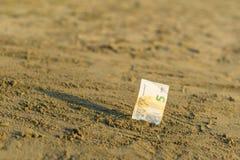 Billet de banque de la valeur de l'euro cinq dans le le sable sur la plage Concept de voyage et de vacances bon marché image libre de droits