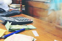 Billet de banque thaïlandais de calculatrice et d'argent avec le papier blanc de carnet, stylo sur le bureau en bois de table à l Photo libre de droits