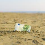 Billet de banque de valeur de cent euros dans le le sable sur la plage Concept de voyage et de vacances bon marché images stock