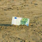 Billet de banque de valeur de cent euros dans le le sable sur la plage Concept de voyage et de vacances bon marché image stock