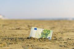 Billet de banque de valeur de cent euros dans le le sable sur la plage Concept de voyage et de vacances bon marché image libre de droits