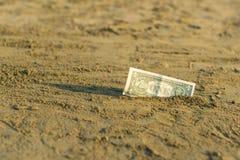 Billet de banque de valeur d'un dollar dans le le sable sur la plage Concept de voyage et de vacances bon marché photographie stock