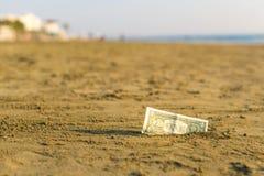 Billet de banque de valeur d'un dollar dans le le sable sur la plage Concept de voyage et de vacances bon marché image stock