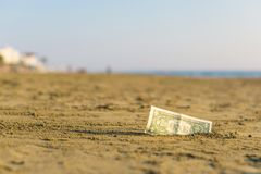 Billet de banque de valeur d'un dollar dans le le sable sur la plage Concept de voyage et de vacances bon marché images stock