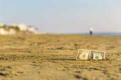 Billet de banque de valeur d'un dollar dans le le sable sur la plage Concept de voyage et de vacances bon marché photographie stock libre de droits
