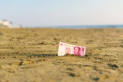 Billet de banque de valeur d'un yuan de la Chine dans le le sable sur la plage Concept image libre de droits