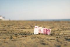 Billet de banque de valeur d'un yuan de la Chine dans le le sable sur la plage Concept photographie stock libre de droits