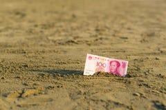 Billet de banque de valeur d'un yuan de la Chine dans le le sable sur la plage Concept photo stock