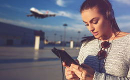 Billet de commande de femme par le comprimé sur l'aéroport Photo stock