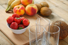 Billet for fruit cocktail on a cutting board bananas, strawberries, peach. Stock Photography