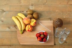 Billet for fruit cocktail on a cutting board bananas, strawberries, peach. Stock Images