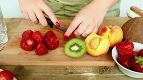 Billet for fruit cocktail on a cutting board bananas, strawberries, peach. A woman is running a knife with a strawberry. Moving the camera from right to left stock video