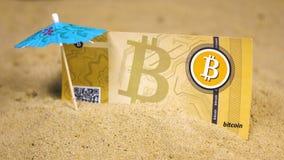 Billete de banco de Bitcoin en arena cerca del pincho azul del paraguas almacen de metraje de vídeo