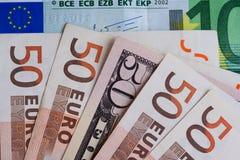 Billete de banco de 50 dólares entre billetes de banco 50 euros Imagen de archivo libre de regalías