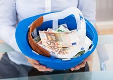 Billete de banco de Holding Hardhat With del empresario Imágenes de archivo libres de regalías