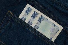 Billete de banco de la moneda de los yenes japoneses en un bolsillo trasero de un jea del dril de algodón Imagenes de archivo