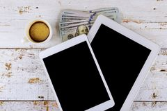 Billete de banco del d?lar americano y taza de caf? con el material de oficina financiero de la tableta digital en el fondo de ma imagenes de archivo