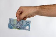 Billete de banco del dólar australiano 10 en mano trasera Imágenes de archivo libres de regalías