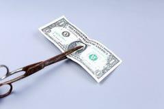 Billete de banco del dólar y tijeras Foto de archivo libre de regalías