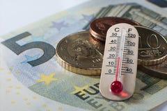 Billete de banco del euro cinco con algunas monedas y un termómetro Imagen de archivo