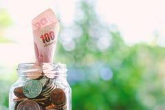Billete de banco, dinero tailandés de la moneda de 100 baht que crece del ja de cristal Fotografía de archivo libre de regalías
