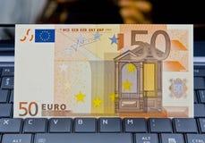 Billete de banco euro en el teclado de la computadora portátil Fotografía de archivo