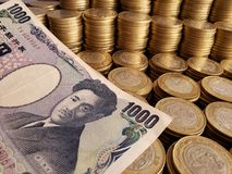 Billete de banco japon?s de 1000 yenes y monedas apiladas de diez Pesos mexicanos fotografía de archivo libre de regalías