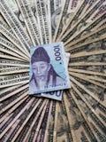 billete de banco surcoreano de 1000 ganados y del fondo con las cuentas de dólares americanas