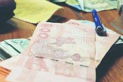 Billete de banco tailandés de la calculadora y del dinero con el papel blanco del cuaderno, pluma en oficina de madera de la tabl Foto de archivo