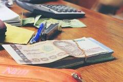 Billete de banco tailandés de la calculadora y del dinero con el papel blanco del cuaderno, pluma en oficina de madera de la tabl Foto de archivo libre de regalías