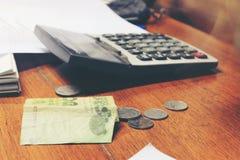 Billete de banco tailandés de la calculadora y del dinero con el papel blanco del cuaderno, pluma en oficina de madera de la tabl Fotos de archivo