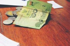 Billete de banco tailandés de la calculadora y del dinero con el papel blanco del cuaderno, pluma en oficina de madera de la tabl Imagenes de archivo