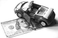 Billete de banco y coche rojo Foto de archivo