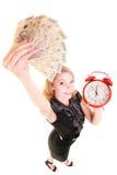 Billete de banco y despertador del dinero del pulimento de la tenencia de la mujer Fotografía de archivo