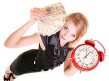 Billete de banco y despertador del dinero del pulimento de la tenencia de la mujer Imagenes de archivo