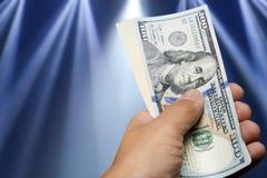 Billete de dólar del control ciento de la mano sobre luces hermosas Imagen de archivo libre de regalías