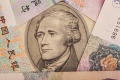 Billete de dólar diez rodeado por el chino Yuan Fotografía de archivo