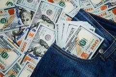 billete de dólar 100 que se pega hacia fuera de un bolsillo azul de la mezclilla Imagen de archivo libre de regalías