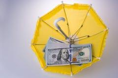 Billetes de banco americanos del dólar colocados en un paraguas Foto de archivo libre de regalías
