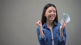 Billetes de banco asiáticos emocionados del dólar de la demostración de la mujer en la cámara, ganador de lotería, fortuna almacen de video