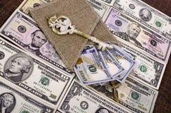 Billetes de banco cientos dólares, arpilleras y llaves Fotografía de archivo libre de regalías