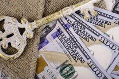 Billetes de banco cientos dólares, arpilleras y llaves Imágenes de archivo libres de regalías