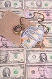 Billetes de banco cientos dólares y otros relojes de la denominación, de la arpillera y de bolsillo Imagen de archivo libre de regalías